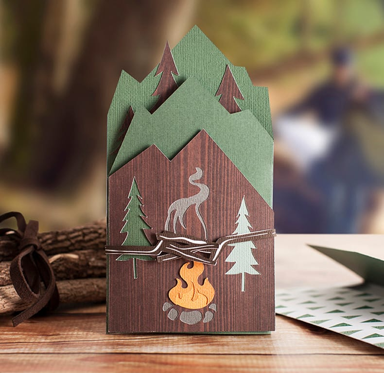 A handmade card decorated with trees and a campfire sits on a desk.