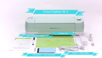 The Cricut Explore Air 2 comes with the machine, cutting mat, power and USB cables, pen and accessory holder, blade and blade holder, and cardstock and vinyl samples.