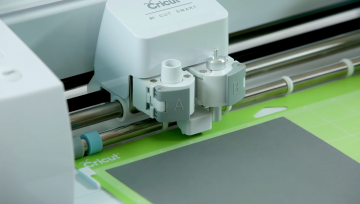Loading a cutting mat into a Cricut Explore Air 2 vinyl cutting machine
