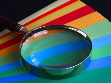 A magnifying glass on colored paper.
