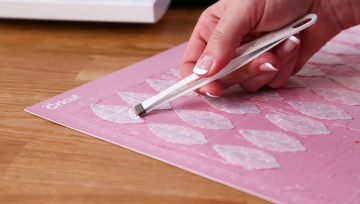 Use Broad-tipped tweezers to remove your material from the pink cutting mat
