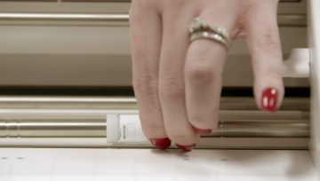 a woman slides the white pinch rollers on the roller bar