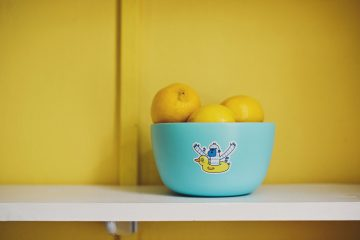 A friendly monster sticker on a blue bowl full of lemons
