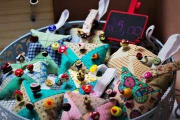 A bowl of colorful pincushions for sale at a crafts fair