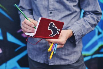 A man writes in a small red notebook decorated with a pixel dinosaur sticker