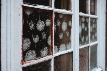 White snowflakes decorate the interior of a rustic window