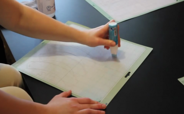 A woman applies Zig 2-way Glue to her Cricut mat to make it sticky again
