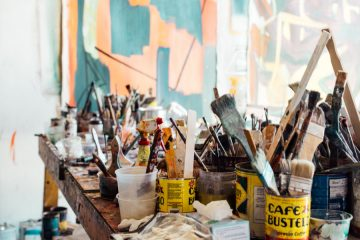A messy craft room with paint brushes soaking