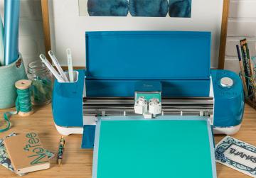 A bright Blue Cricut Explore Air 2 cuts vinyl on a desk full of crafting supplies.