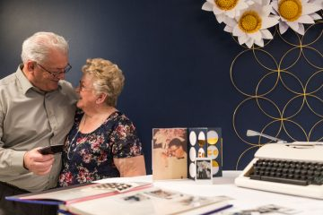 A happy couple celebrates their 50th anniversary with giant paper daisies.