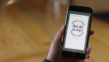 "A woman uses Cricut Design Space on her phone, selecting a graphic that reads, ""Make Life Beautiful."""