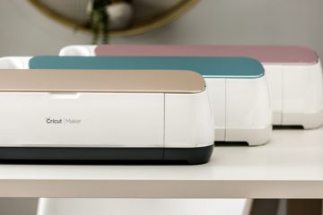 The Cricut Maker is shown in three different colors: champagne, rose, and blue.
