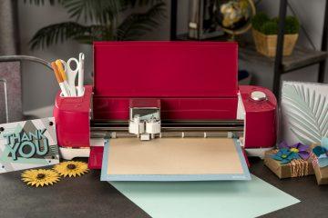 A raspberry Cricut Explore Air 2 sits on a desk cutting vinyl.