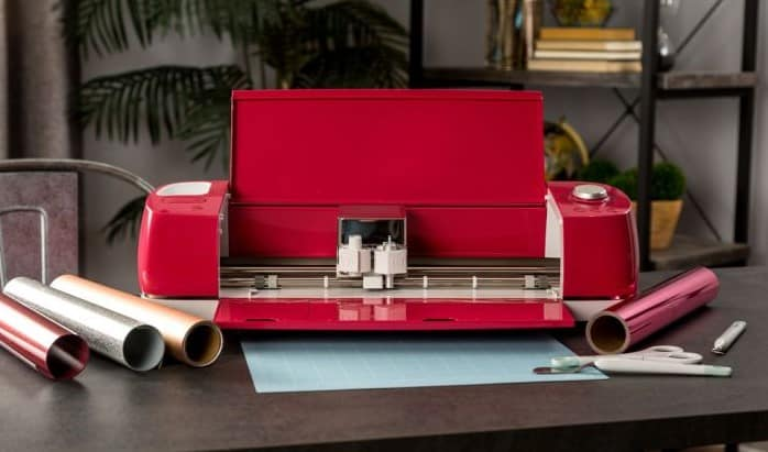 A bright red Explore Air 2 sits open on a desk with vinyl and cutting mat.