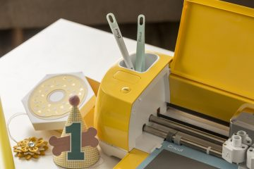 A bright yellow Cricut Explore Air 2 holds tools in the convenient accessory storage.